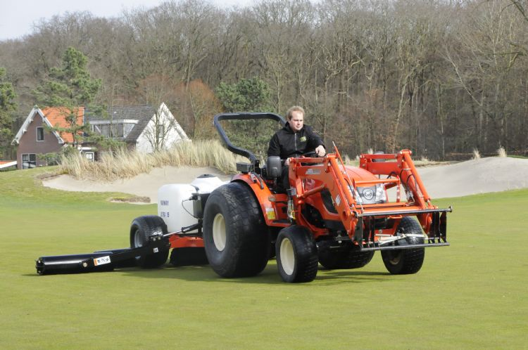 Willem Slats junior demonstreert de fairwayroller op Groendael.