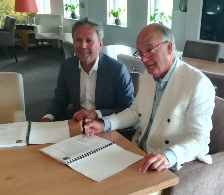 Arie-Jan de Ridder (De Ridder) en Ron de Graaf (voorzitter Golfclub Houtrak) tekenen het contract.
